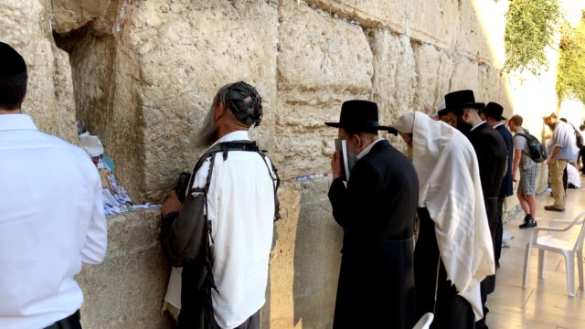 a man in tattered clothing prays at the wailing wall dressing in sackcloth is a traditional way of mourning the destruction of the ancient jewish... - orthodox judaism stock videos & royalty-free footage
