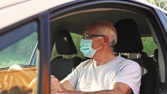 vídeos y material grabado en eventos de stock de hombre en el coche de conducción durante el cóvido - taxista