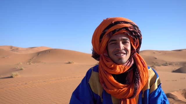 Man in the desert wearing a traditional headscarf smiling
