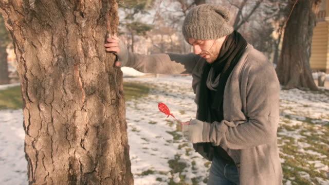 Homme dans le parc tenant une forme de coeur et frapper sa tête avec elle pense à ses problèmes relationnels
