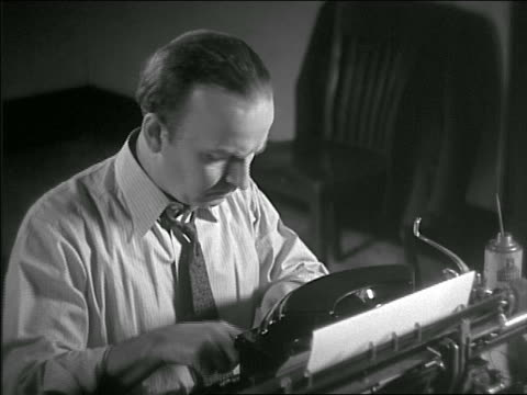 b/w 1936 man in tie typing at typewriter with serious expression - プレスルーム点の映像素材/bロール