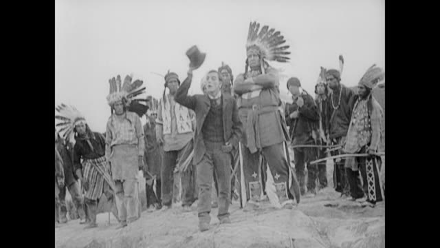 1922 Man (Buster Keaton) in top hat and tails falls into river to escape American Indians