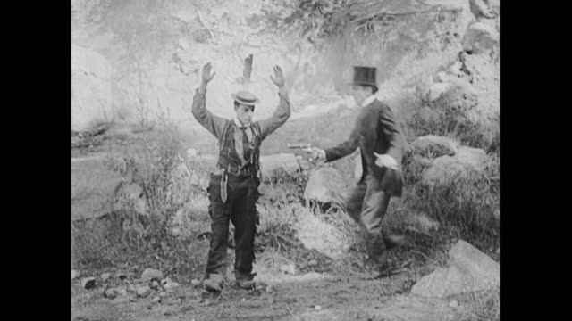 1922 man in top hat forces second man (buster keaton) to exchange clothes at gunpoint - bretella video stock e b–roll
