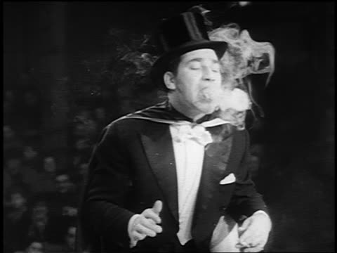 vídeos y material grabado en eventos de stock de b/w 1955 pan man in top hat + tails blowing smoke rings in circus - sombrero de copa