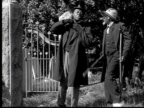 1916 b&w ms man in top hat walking and putting older man with injured foot down from piggyback position at gate to graveyard/ injured man attempting to get on man's back again and falling  - aiming stock videos and b-roll footage