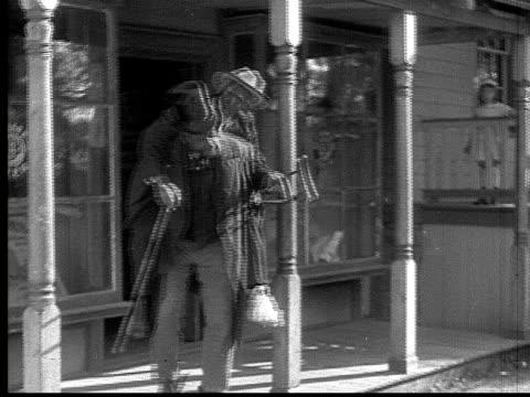 stockvideo's en b-roll-footage met 1916 b&w ms man in top hat walking out of building riding older, injured man piggyback  - compleet pak