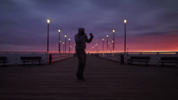 Man In Tracksuit Shadow Boxing with Weights on a Seaside Pier at Dusk - Wide Shot in 4K.
