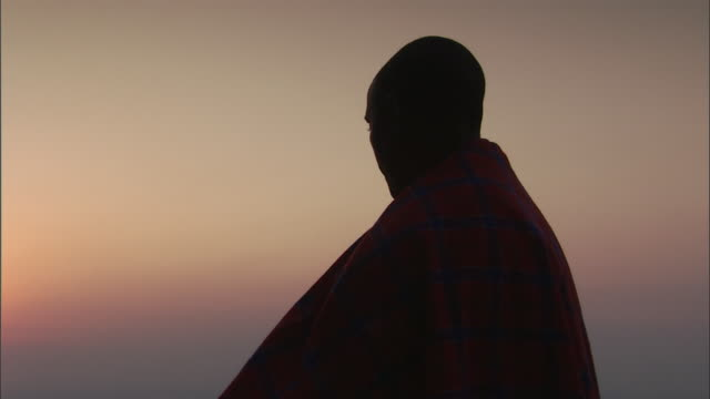 vidéos et rushes de mcu pan man in traditional african massai robe gazes down  valley and sunset / kigoma, tanzania - endroit isolé