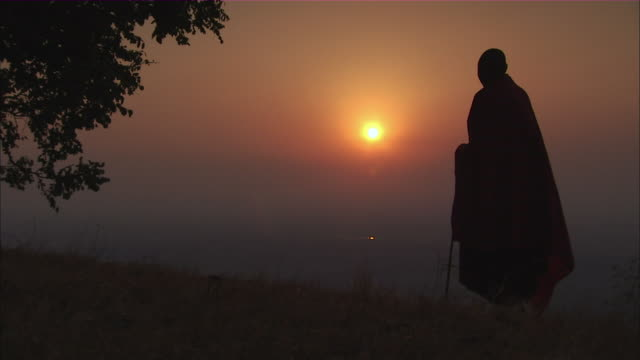 ms man in traditional african massai robe gazes down  valley and sunset / kigoma, tanzania - tanzania stock videos & royalty-free footage