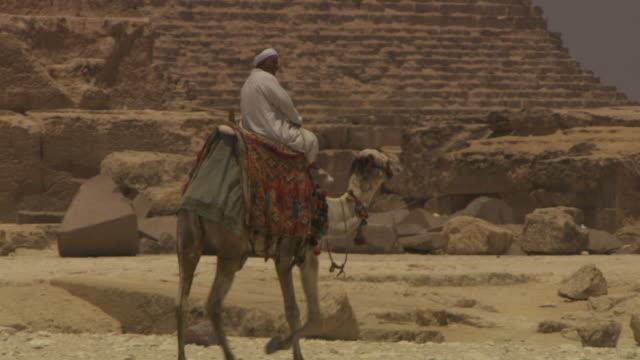 vídeos de stock, filmes e b-roll de a man in traditional clothing rides a camel next to one of giza's pyramids, egypt. - visita