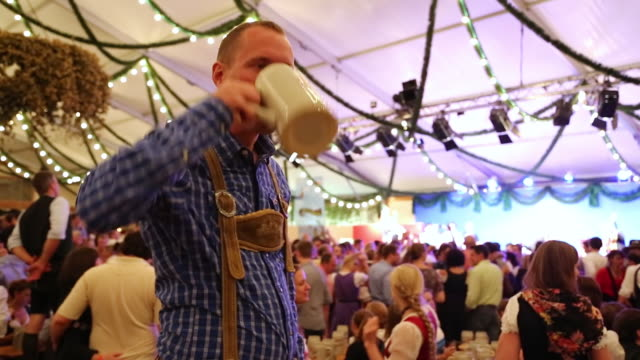 ms man in traditional dress drinking from beer jug and dancing at traditional oktoberfest inside tent / munich, bavaria, germany  - zelt stock-videos und b-roll-filmmaterial