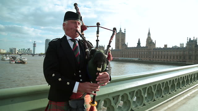 man in traditional dress plays bagpipes on westminster bridge with the palace of westminster in the background. - house of commons stock videos & royalty-free footage