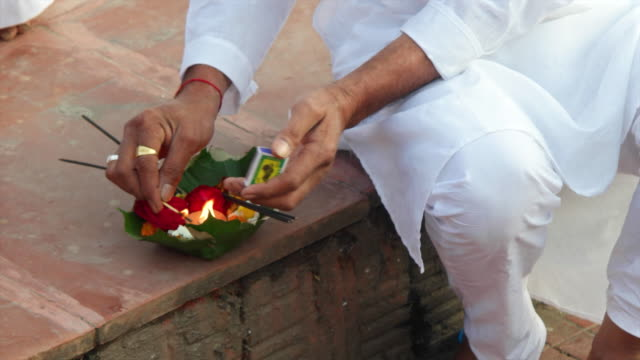 A man in traditional white clothing lights a diya at the ghats in Haridwar