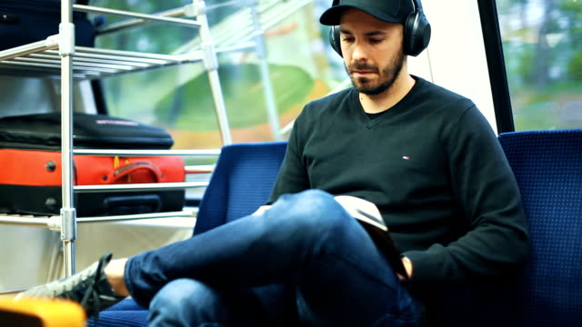 Man in train reading book