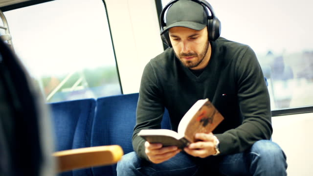 man in train reading book - contented emotion stock videos & royalty-free footage