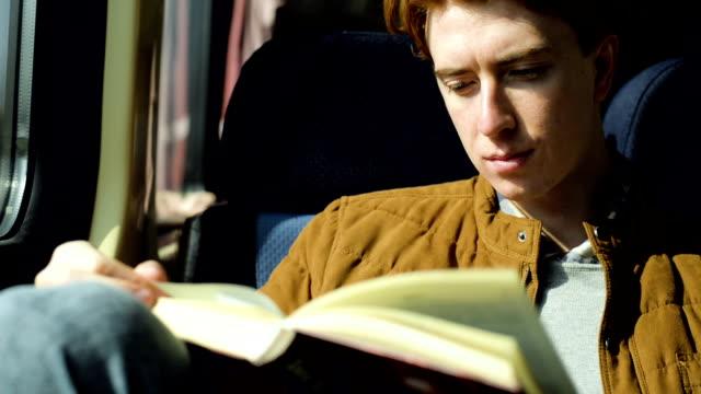 Man in train reading book