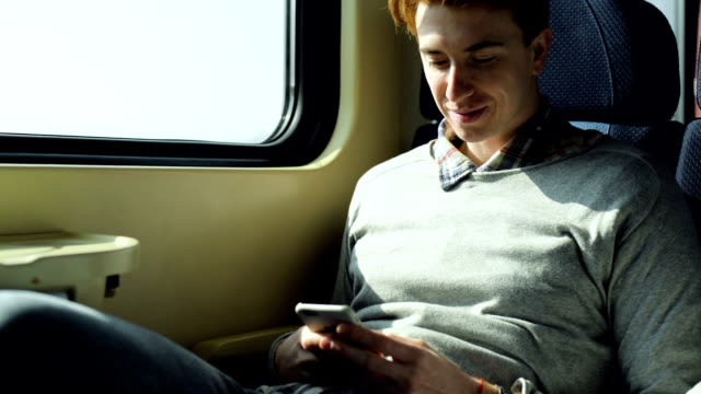 Man in train using phone