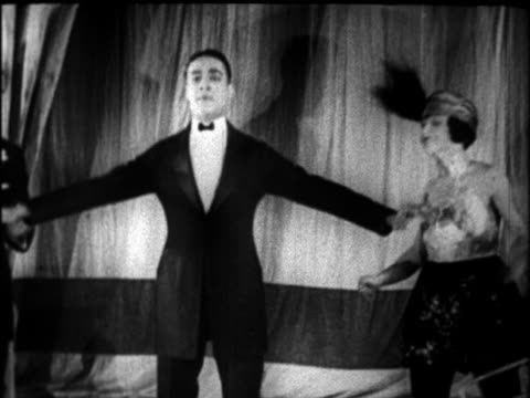 B/W 1927 man in tuxedo dancing on stage as woman looks on / newsreel