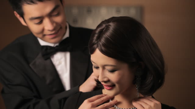 CU Man in tuxedo putting diamond necklace on young women's neck / China