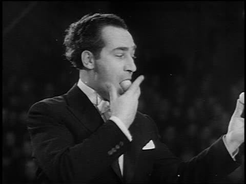 B/W 1955 man in tuxedo taking many balls out of mouth in circus