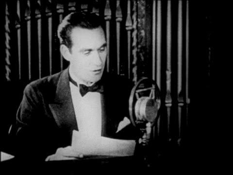 B/W 1927 man in tuxedo talking into microphone in radio studio / newsreel