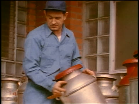 1957 man in uniform + cap lifting metal cannister from group of cannisters outside of building - anno 1957 video stock e b–roll