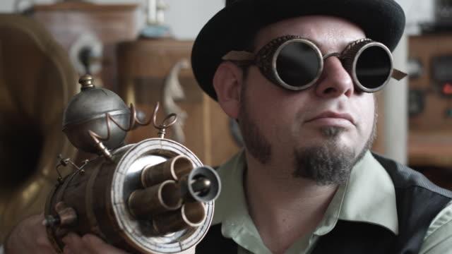 cu man in victorian steampunk outfit pointing victorian futuristic gun at camera, middletown, connecticut, usa - ziegenbart stock-videos und b-roll-filmmaterial