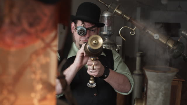 MS Man in Victorian Steampunk outfit pointing Victorian futuristic gun at camera, brain in jar and steam in foreground, Middletown, Connecticut, USA