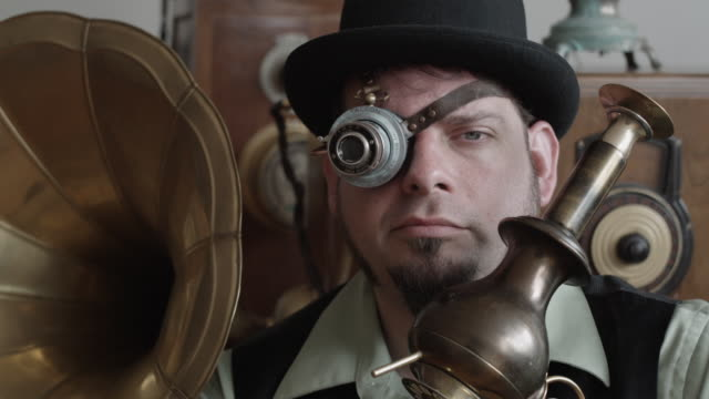 CU Man in Victorian Steampunk outfit wearing monocle and holding gun, Middletown, Connecticut, USA