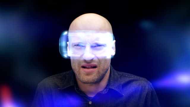 man in virtual reality glasses frowning and closing his eyes. looking at imaginary, disgusting object - colore isolato video stock e b–roll