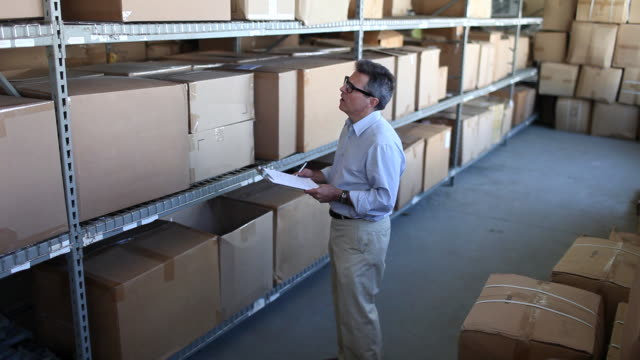 """""""ms man in warehouse full of boxes taking stock on  clipboard / brooklyn, new york, united states"""" - only mature men stock videos & royalty-free footage"""