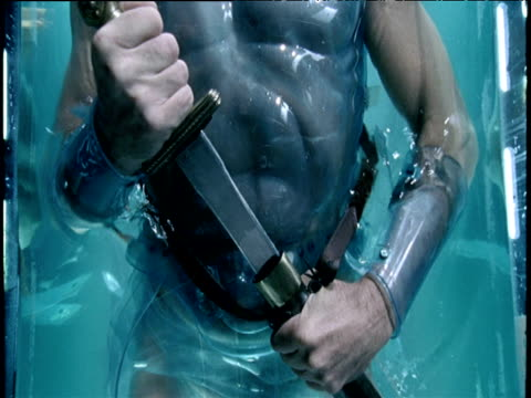 man in water wearing plastic armour removes dagger from sheath - dagger stock videos & royalty-free footage