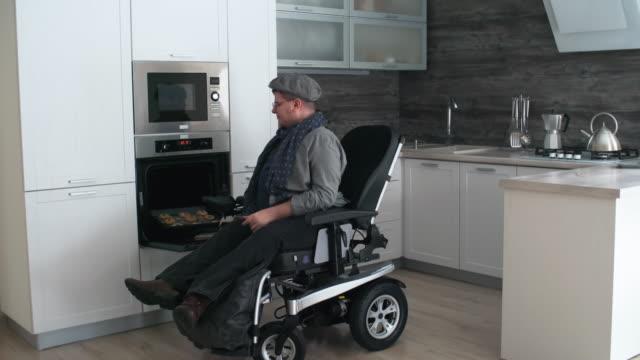 man in wheelchair baking - オーブンの天板点の映像素材/bロール