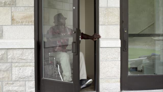 Man in wheelchair exiting building door.