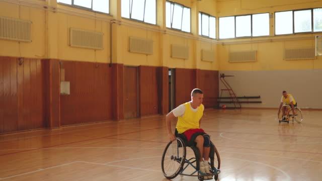 man in wheelchair shooting on hoop in sport hall - paraplegic stock videos & royalty-free footage