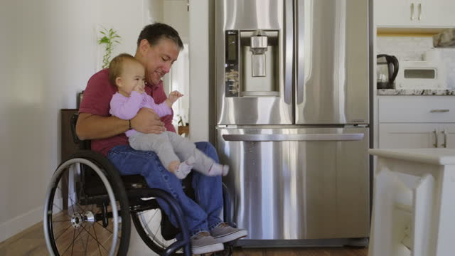man in wheelchair with a baby in a home - war veteran stock videos & royalty-free footage
