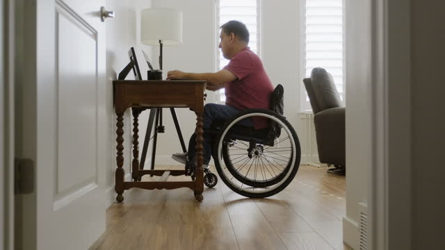 man in wheelchair working in a home office - war veteran stock videos & royalty-free footage