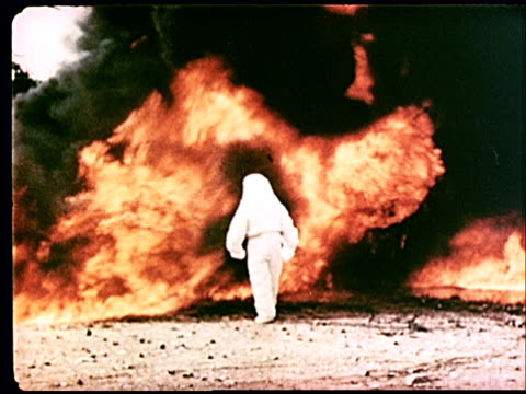 vídeos de stock, filmes e b-roll de 1962 montage ws man in white fireproof suit walking into fire through black smoke - prelinger archive