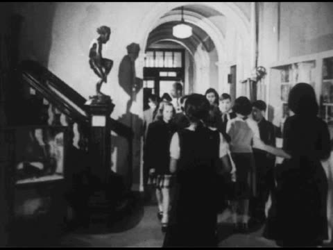 vidéos et rushes de / man in white lab coat exits a car with box-like object as a crowd of children surrounds him / interior hall of building with arched doorways /... - blouse de laborantin