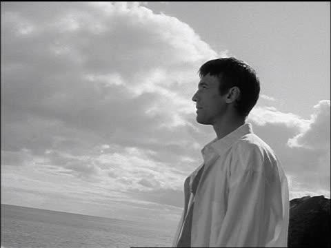vídeos y material grabado en eventos de stock de b/w profile man in white shirt stands + poses, looking over ocean - camisa blanca