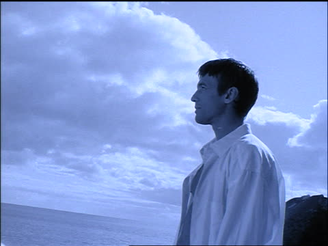 b/w blue profile man in white shirt stands + poses, looking over ocean - manipolazione di colore video stock e b–roll