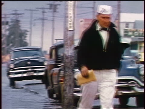 1957 man in white uniform + hat walking past parked cars on street / feature - anno 1957 video stock e b–roll