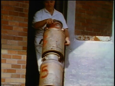 1957 man in white uniform + hat  wheeling cannisters out of building on hand truck - anno 1957 video stock e b–roll