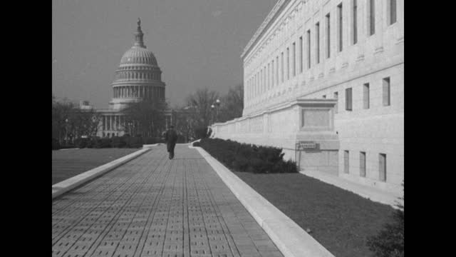 man in winter coat and hat walking away from camera, toward the united states capitol in bg; smoke from his mouth is visible in cold air / note:... - オーバーコート点の映像素材/bロール