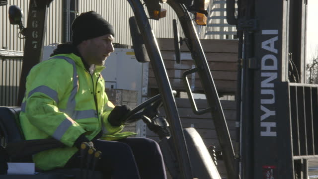 stockvideo's en b-roll-footage met a man in yellow high-visibility workwear concentrates as he manoeuvres a forklift vehicle at a fruit distribution warehouse in kent, uk. - heftruck