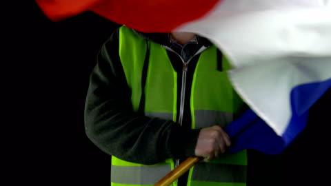 vidéos et rushes de homme dans le gilet jaune agitant le drapeau de france - grève