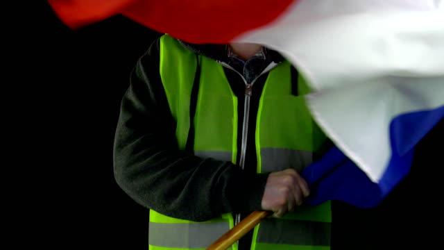 stockvideo's en b-roll-footage met man in geel vest zwaaien frankrijk vlag - franse vlag