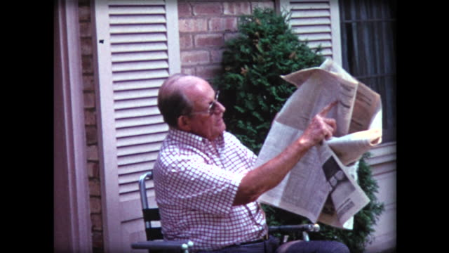 vídeos de stock e filmes b-roll de 1974 man indicates his stocks went up in newspaper - jornal
