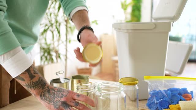 vídeos de stock e filmes b-roll de man indoors at home separating glass and metal for recycling. - reutilizável