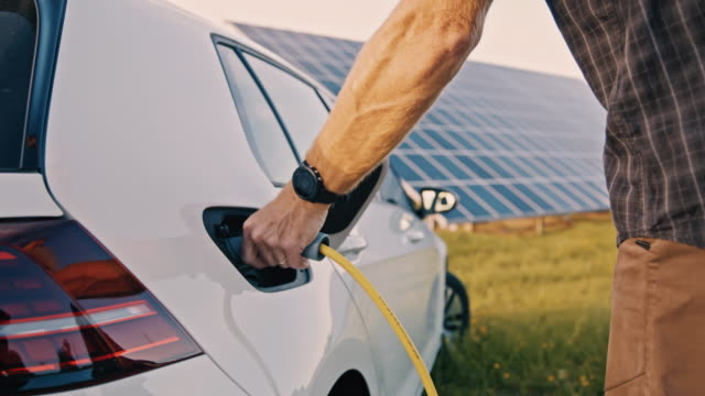 slo mo man inserting an ev plug into the vehicle inlet for charging from solar energy - inserting stock videos & royalty-free footage